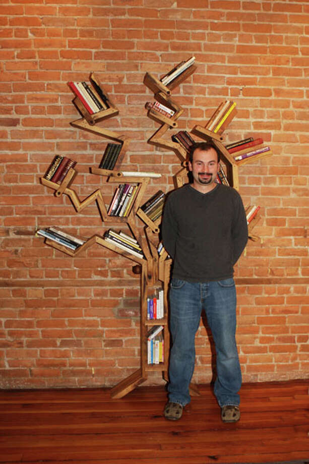 "Fine furniture maker Jim Smith creates materpieces of functional art from his woodworking shop in Schuylerville. Pictured above, Smith stands in front of his modifiable book tree, ""fiction-non."" (Krishna Hill/Life@Home) Click here to read the story."