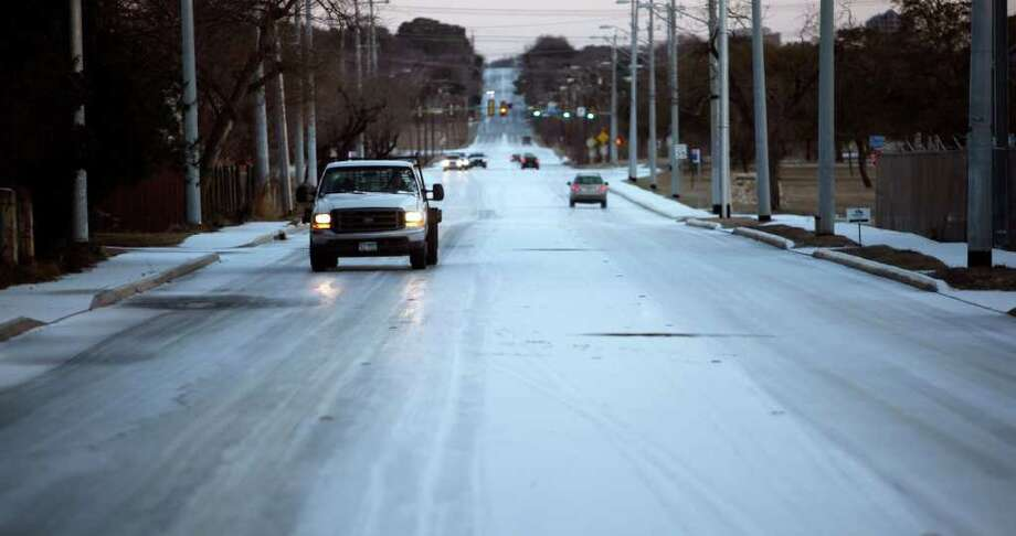 A truck makes its way along a snow-covered McCullough Avenue near Basse Road Friday morning Feb. 4, 2011. Photo: WILLIAM LUTHER, Wluther@express-news.net / © 2011 San Antonio Express-News