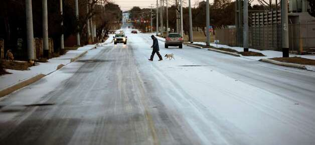 A man walks across a snow-covered McCullough Avenue Friday morning Feb. 4, 2011 near the intersection of Basse Road. Photo: WILLIAM LUTHER, Wluther@express-news.net / © 2011 San Antonio Express-News