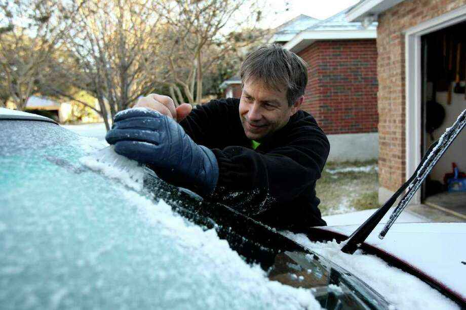 Before he can leave in the morning, Melvin Soderlund has to scrape off the ice and snow that fell on his windshield. Photo: HELEN L. MONTOYA, SAN ANTONIO EXPRESS-NEWS / hmontoya@express-news.net