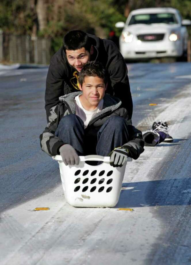 Joey Hite gets a push from brother Steven Ybarra while riding a clothes basket down a hill on Babcock Road. Photo: Bob Owen, San Antonio Express-News / rowen@express-news.net