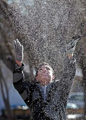 metro daily - Joey Hite throws handfulls of snow in the air as he plays in the white stuff in front of his home on Babcock Rd. near Wilson, Friday, Feb. 4, 2011. Photo Bob Owen/rowen@express-news.net Photo: Bob Owen, San Antonio Express-News / rowen@express-news.net