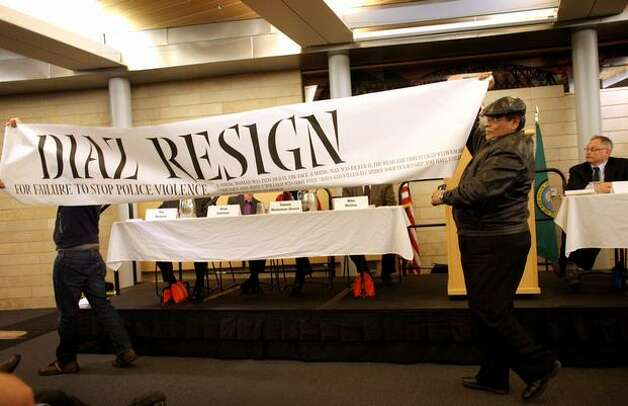 Federico Martinez, left, and Juan Jose Bocanegra interrupt a meeting with a banner calling for Seattle Police Chief John Diaz, far right, to resign during a panel discussion on police accountability on Thursday, February 3, 2011 at Seattle City Hall. Recent controversial police incidents prompted the at times rowdy forum. Photo: Joshua Trujillo/seattlepi.com