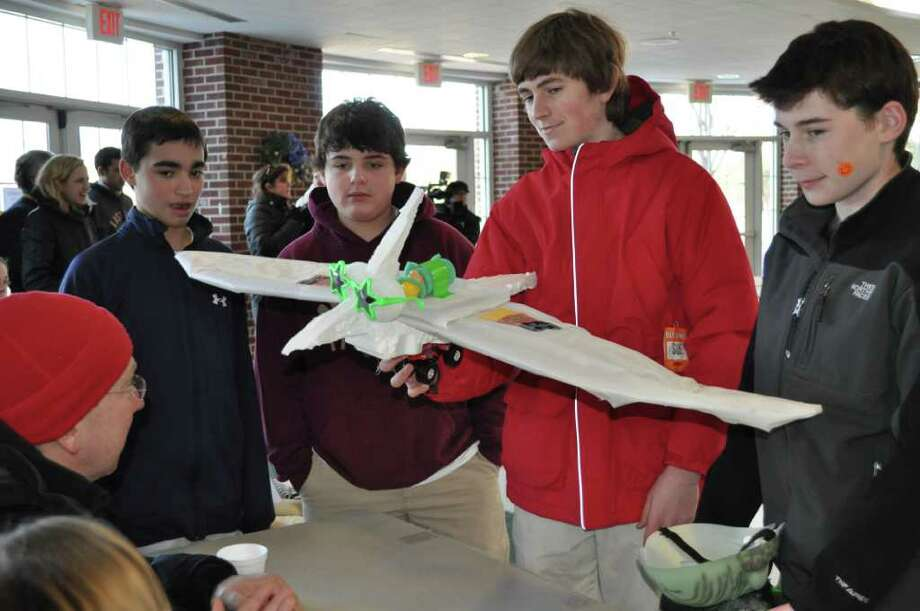 Team Dinosaurier (from left, Drew Costantino, Christian Romanello, Danny Ross, and Jonathan Winter) show MMS teacher and judge Peter Martin their flying creation. Photo: Contributed Photo / Darien News