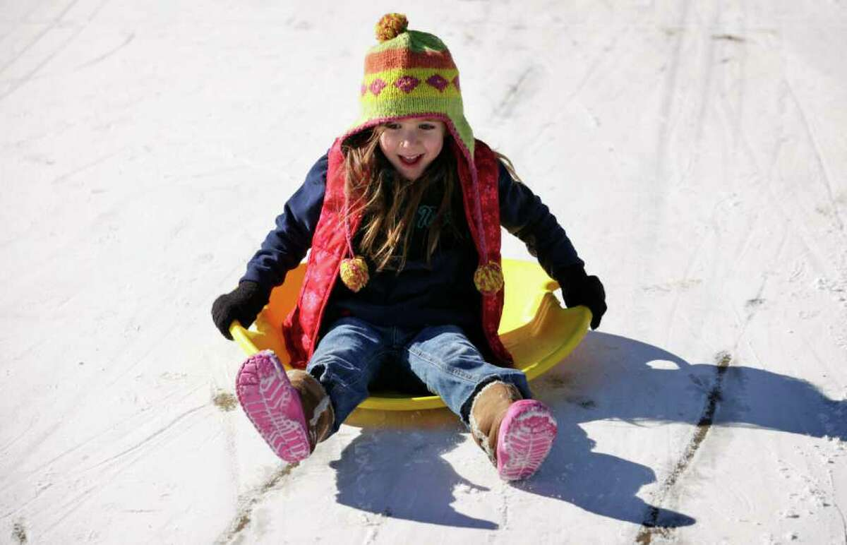 Metro daily - Sydni Sage, 5, sleds down a driveway on Crossette Dr, after a thin blanket of snow covers San Antonio, Friday, Feb. 4, 2011. photo Bob Owen/rowen@express-news.net