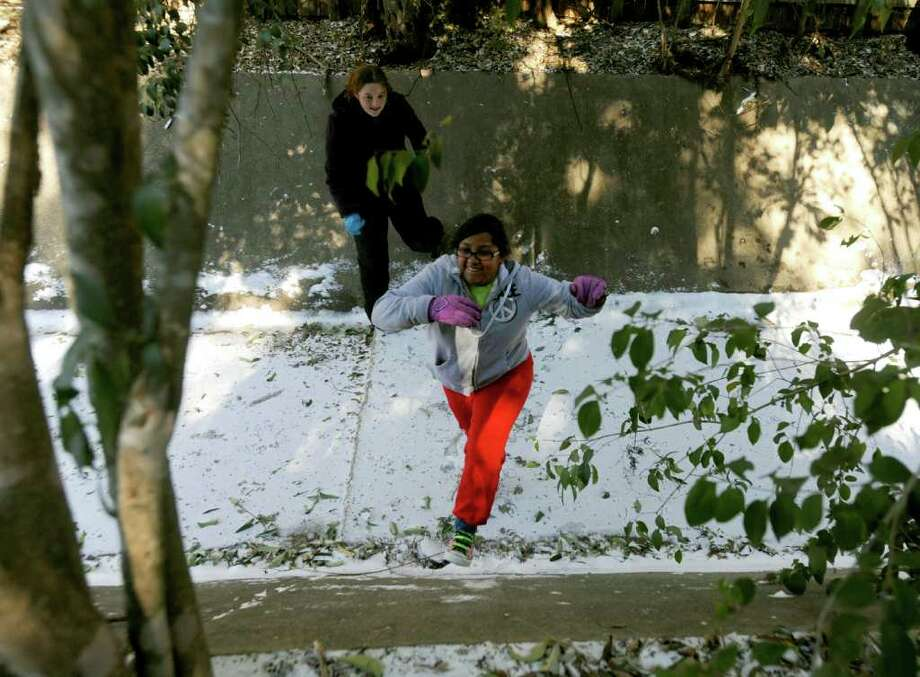 Amanda Villegas, front, and her friend, Katie Shute, play in a ditch in the Harmony Hills neighborhood after an overnight snow fall in San Antonio on Friday, Feb. 4, 2011. BILLY CALZADA / gcalzada@express-news.net  shute cq Photo: BILLY CALZADA, SAN ANTONIO EXPRESS-NEWS / gcalzada@express-news.net