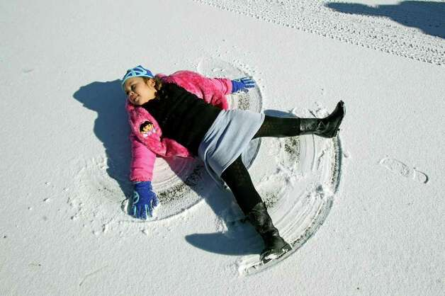 METRO   Kaylie Juergens (this is correct sp) takes time to make a snow angel while walking with her father in Gruene as snow accumulation shows in the New Braunfels area on February 4, 2011. Tom Reel/Staff Photo: TOM REEL, SAN ANTONIO EXPRESS-NEWS / © 2010 San Antonio Express-News