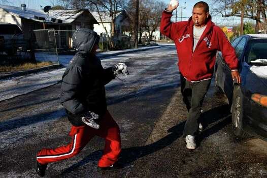 """METRO - """"This is war,"""" yells Efren Sanchez, 12, left, as his uncle, Juan Garcia, right, throws a snowball in retaliation for Efren's previous attack as they enjoy the snow in San Antonio on Friday, Feb. 4, 2011. LISA KRANTZ/lkrantz@express-news.net Photo: LISA KRANTZ, SAN ANTONIO EXPRESS-NEWS / SAN ANTONIO EXPRESS-NEWS"""