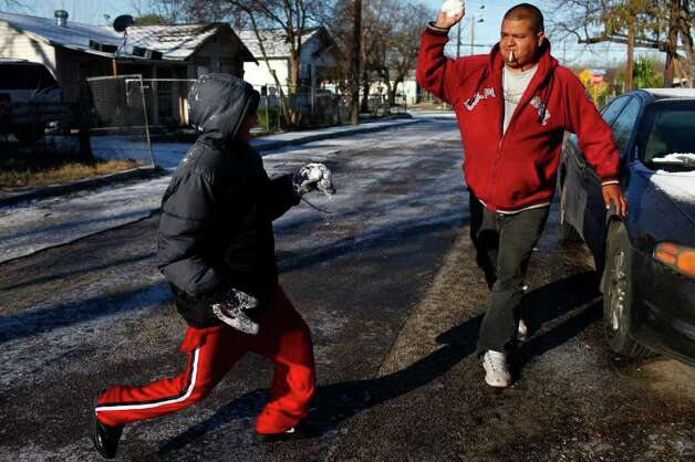 "METRO - ""This is war,"" yells Efren Sanchez, 12, left, as his uncle, Juan Garcia, right, throws a snowball in retaliation for Efren's previous attack as they enjoy the snow in San Antonio on Friday, Feb. 4, 2011. LISA KRANTZ/lkrantz@express-news.net Photo: LISA KRANTZ, SAN ANTONIO EXPRESS-NEWS / SAN ANTONIO EXPRESS-NEWS"