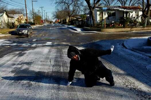 METRO - Sergio Hernandez, 11, laughs after slipping on the icy street during a snowball fight with his family in San Antonio on Friday, Feb. 4, 2011. LISA KRANTZ/lkrantz@express-news.net Photo: LISA KRANTZ, SAN ANTONIO EXPRESS-NEWS / SAN ANTONIO EXPRESS-NEWS