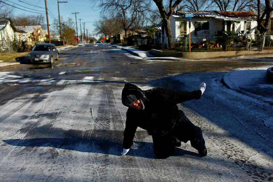METRO - Sergio Hernandez, 11, laughs after slipping on the icy street during a snowball fight with his family in San Antonio on Friday, Feb. 4, 2011. LISA KRANTZ/lkrantz@express-news.net Photo: LISA KRANTZ, SAN ANTONIO EXPRESS-NEWS / SAN ANTONIO EXPRESS-NEWS