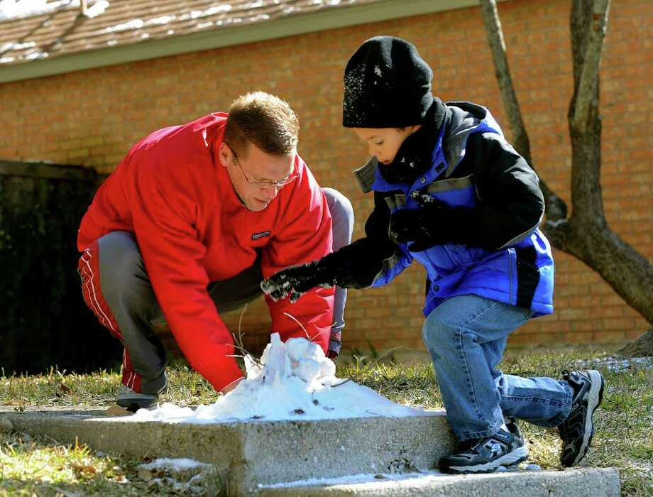 "Chad Theilengerdes helps his son, Landon, 5, build a ""snow town"" on the steps of their Churchill Estates home after an overnight snowfall in San Antonio on Friday, Feb. 4, 2011. BILLY CALZADA / gcalzada@express-news.net Photo: BILLY CALZADA, SAN ANTONIO EXPRESS-NEWS / gcalzada@express-news.net"