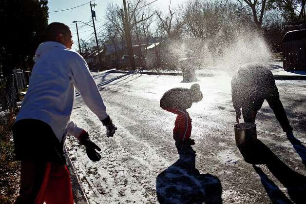 METRO -Ramon Alonso, 16, throws a snowball at his brother, Efren Sanchez, 12, and their mother, Janet Puente, right, as they enjoy the snow in San Antonio on Friday, Feb. 4, 2011. LISA KRANTZ/lkrantz@express-news.net Photo: LISA KRANTZ, SAN ANTONIO EXPRESS-NEWS / SAN ANTONIO EXPRESS-NEWS