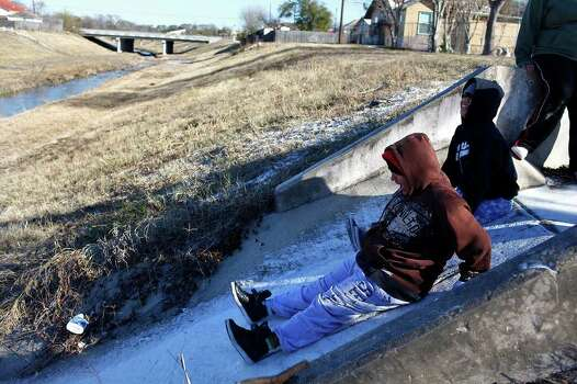 METRO - Priscilla Hernandez, center, and Valerie Hernandez, right, attempt to slide down a snow covered drainage chute in San Antonio on Friday, Feb. 4, 2011. LISA KRANTZ/lkrantz@express-news.net Photo: LISA KRANTZ, SAN ANTONIO EXPRESS-NEWS / SAN ANTONIO EXPRESS-NEWS