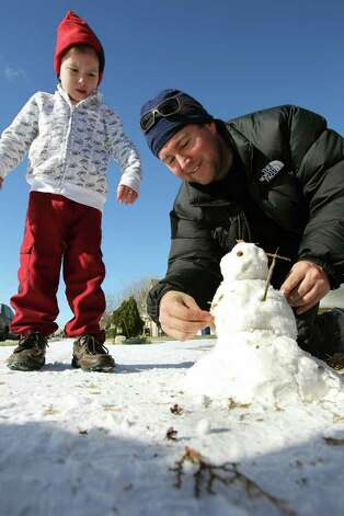 Eric Ream helps son Evan, 4, with the finishing touches on a snowman in the New Braunfels area. Photo: TOM REEL, SAN ANTONIO EXPRESS-NEWS / © 2010 San Antonio Express-News