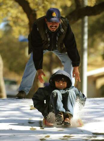 Jacob Contreras, 9, sleds on a cardboard sign with the help of his father, Craig Contreras, in the Churchill Estates neighborhood after an overnight snowfall in San Antonio on Friday, Feb. 4, 2011. BILLY CALZADA / gcalzada@express-news.net Photo: BILLY CALZADA, SAN ANTONIO EXPRESS-NEWS / gcalzada@express-news.net