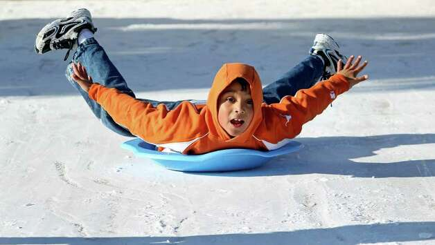 Alex Herrera gets his arms and legs up as he slides down a frozen driveway in the Gruene Crossing subdivision. Photo: TOM REEL, SAN ANTONIO EXPRESS-NEWS / © 2010 San Antonio Express-News