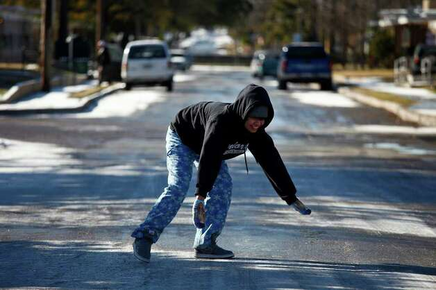METRO - Valerie Hernandez, 18, tries to regain her balance on the icy street after slipping and sliding while playing in the snow with her family in San Antonio on Friday, Feb. 4, 2011. LISA KRANTZ/lkrantz@express-news.net Photo: LISA KRANTZ, SAN ANTONIO EXPRESS-NEWS / SAN ANTONIO EXPRESS-NEWS