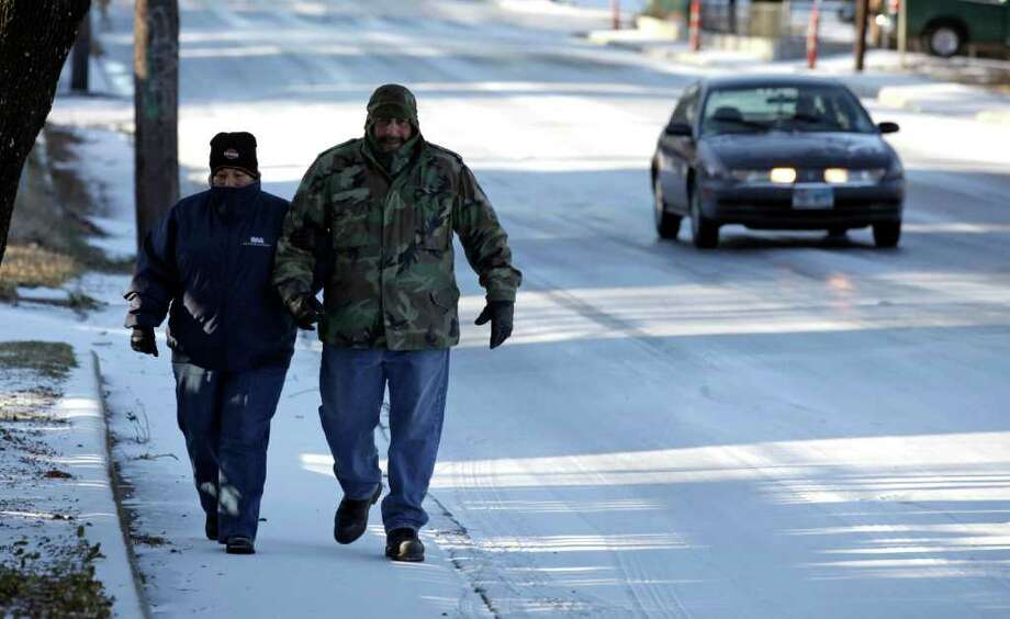 "metro daily - Liza Morin, left, walks with her husband Daniel Morin along a snow and ice covered St. Cloud Rd. near Cromwell, Friday, Feb. 4, 2011. ""We wanted to enjoy it before it melted"" was there comment. Photo Bob Owen/rowen@express-news.net Photo: Bob Owen, San Antonio Express-News / rowen@express-news.net"