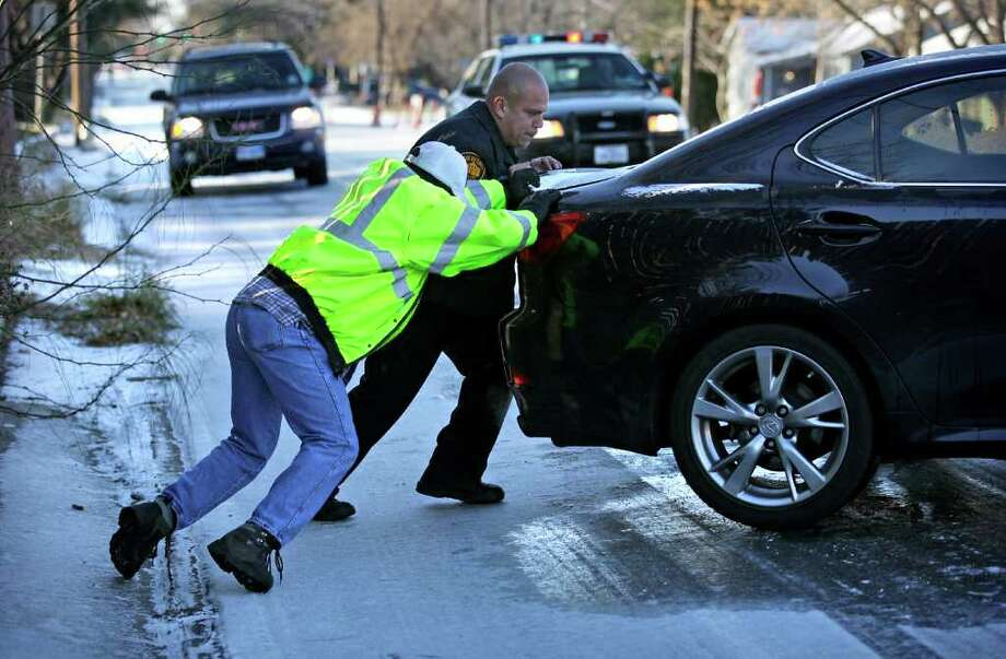 Earl Stephens (foreground) and Police Officer J. Uribe assist a motorist whose car had spun sideways because of icy conditions on St. Cloud Road. Photo: Bob Owen, San Antonio Express-News / rowen@express-news.net
