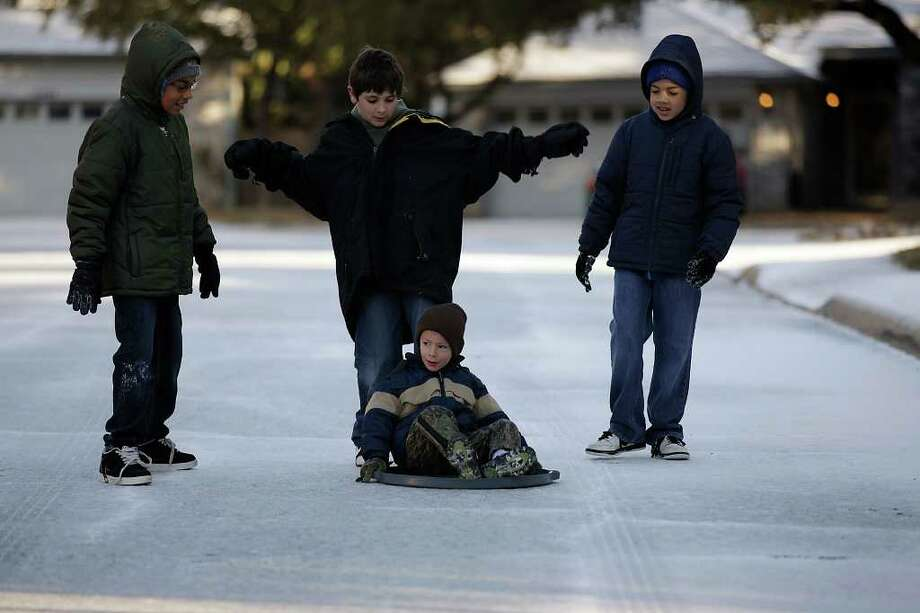 METRO -- Hunter Harkins, 5, rides a trash can top with a little help from Noah Boyett, 11, (pushing behind him) as they and, Jeremiah Garcia, 10, left, and Jason Avalos, 10, play in a frozen landscape at the Villages of Westcreek subdivision on the city's far west side, Friday, Feb. 4, 2011.  JERRY LARA/glara@express-news.net Photo: JERRY LARA, San Antonio Express-News / glara@express-news.net