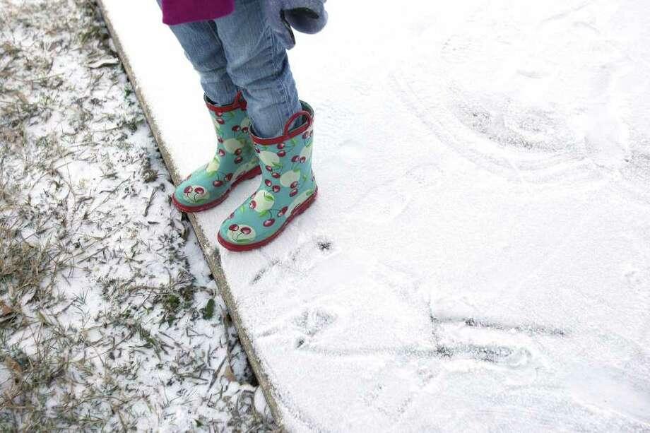 METRO:  Gabby Mauldin, 6, sports her cherry rain slickers as she plays in the snow on Friday Feb. 4, 2011.  HELEN L. MONTOYA/hmontoya@express-news.net Photo: HELEN L. MONTOYA, SAN ANTONIO EXPRESS-NEWS / hmontoya@express-news.net