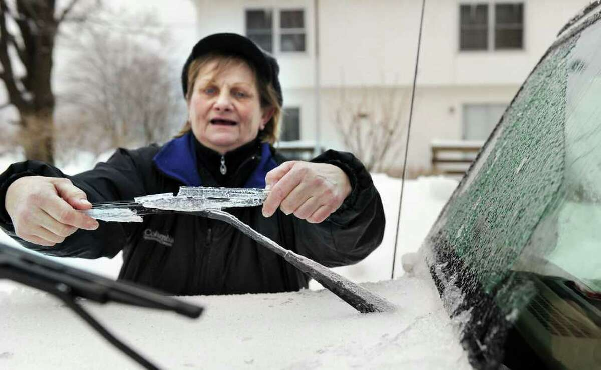 Sue Argenio removes the ice from windshield wipers Wednesday morning on Hospital Avenue in Danbury. Photo taken Wednesday, February 2, 2011.
