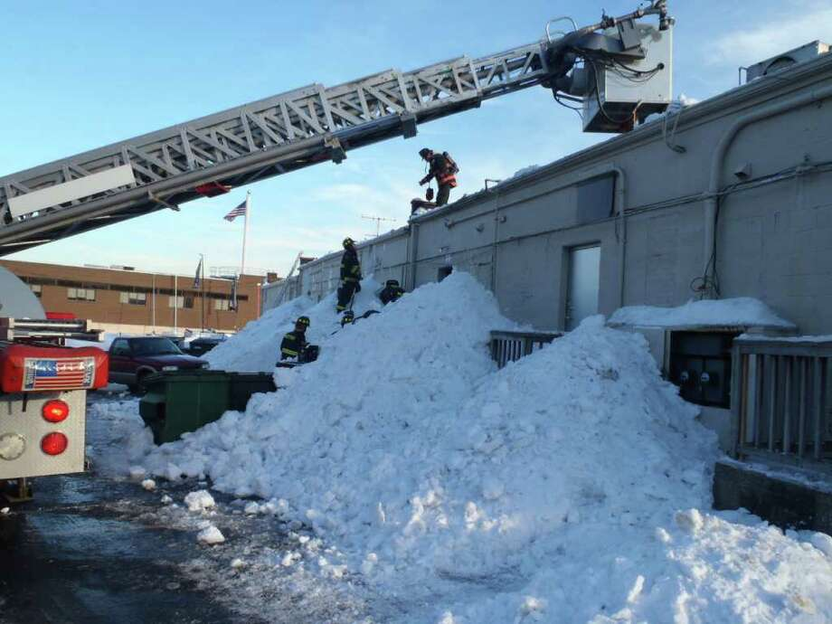 Firefighters scale the roof of the strip mall at 1543 Post Road East in Westport on Friday afternoon to search for a gas leak that was sprung as snow was shoveled off the building's roof. Photo: Contributed Photo/Westport Fire Department / Westport News contributed
