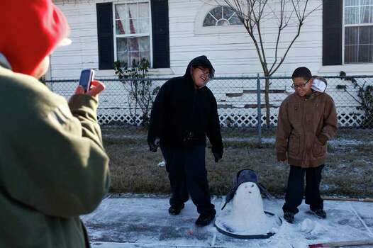 METRO - Priscilla Hernandez, left, photographs her nephews, Sergio Hernandez, 11, and Sebastian Hernandez, 10, as they pose with their   first snowman, sporting a carrot nose, rock eyes, twig arms and Sergio's hat, outside their home in San Antonio on Friday, Feb. 4, 2011. LISA KRANTZ/lkrantz@express-news.net Photo: LISA KRANTZ, SAN ANTONIO EXPRESS-NEWS / SAN ANTONIO EXPRESS-NEWS