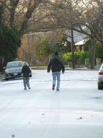 People walk down a snow-covered street in the King William District on Friday, Feb. 4, 2011. Photo: Michael Quintanilla