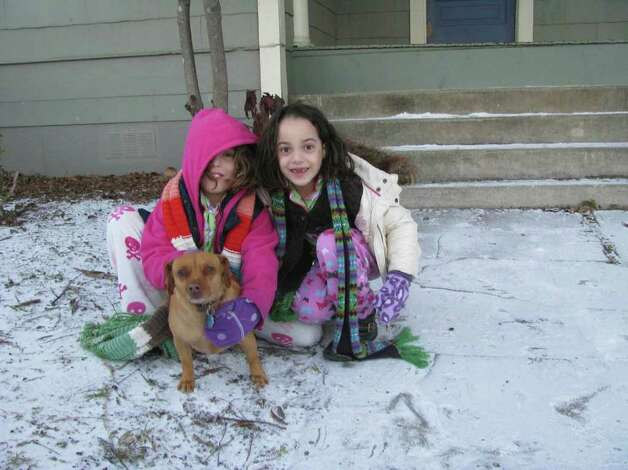 Tati Sigg, 9, and her sister Ale, 6, play in the snow with their dog Pulgi in the King William District on Friday, Feb. 4, 2011. Photo: Michael Quintanilla