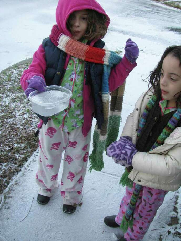 Tati Sigg, 9, and sister Ale, 6, check out the water -- now a block of ice -- they left out for strays in the King William District on Friday, Feb. 4, 2011. Photo: Michael Quintanilla