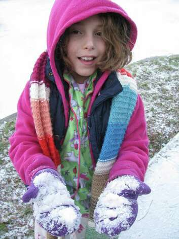 Tati Sigg, 9, gets a handful of snow in the King William District on Friday, Feb. 4, 2011. Photo: Michael Quintanilla