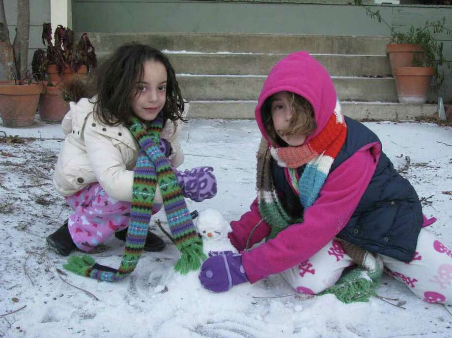 Ale Sigg, 6 (left), helps her sister Tati, 9, build a snowman to celebrate Tati's birthday in the King William District on Friday, Feb. 4, 2011. Photo: Michael Quintanilla