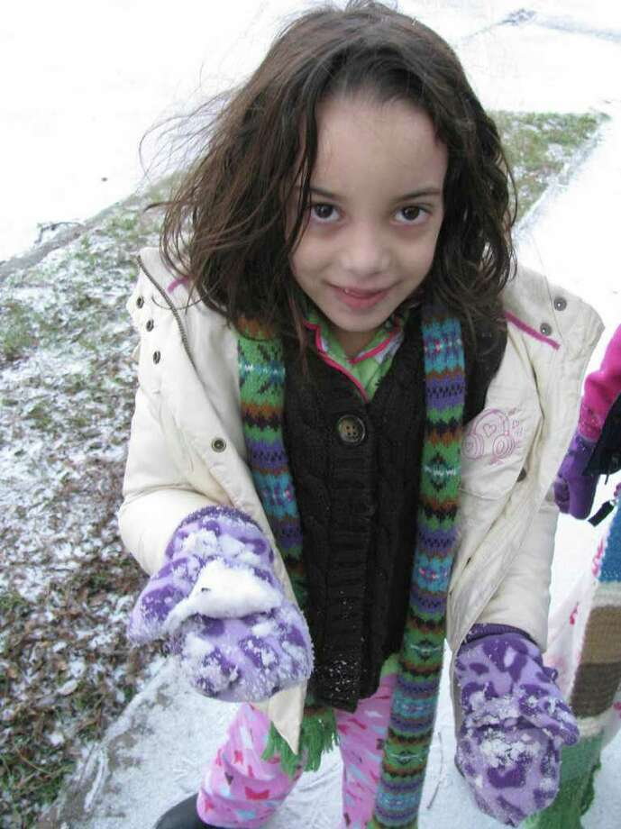 Ale Sigg, 6, collects snow in her mittens in the King William District on Friday, Feb. 4, 2011. Photo: Michael Quintanilla