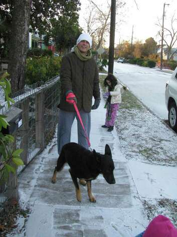 Tirso Sigg and the family dog, Olivia, enjoy a walk in the snow in the King William District on Friday, Feb. 4, 2011. Photo: Michael Quintanilla