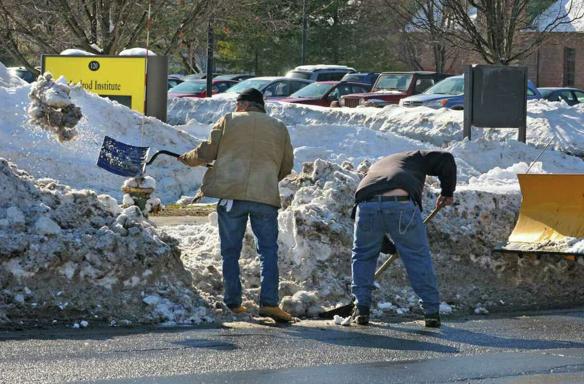 Dan Carey, left, and Scott Seavey of the Department of Health clear out a fire hydrant along New Scotland Avenue in Albany, NY, on February 4, 2011. (Lori Van Buren / Times Union)