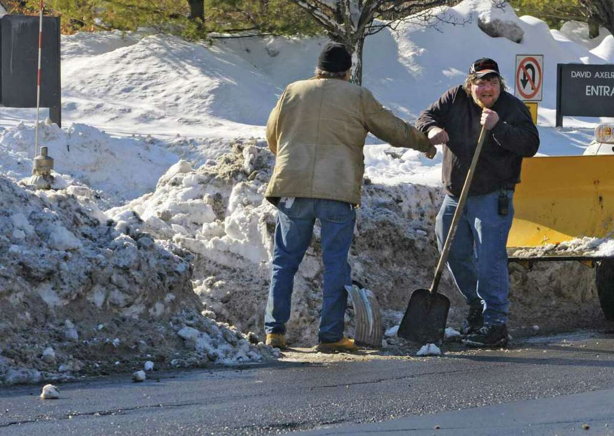 Dan Carey, left, and Scott Seavey of the Department of Health bump fists after clearing out a fire hydrant along New Scotland Avenue in Albany, NY, on February 4, 2011. The men were happy they did not get hit by a car.