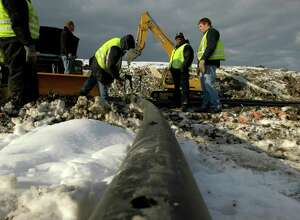 Albany City Landfill employees work on connecting two sections of 4 inch diameter collection pipe at the Rapp Road landfill on Monday, Jan. 10, 2005.  The 4 inch pipe is then inserted in a 12 inch pipe which is then buried under garbage and through a system of piping the methane gas is pulled from the garbage and some of the methane is used for energy porduction and the rest is burned off.  As the landfill fills up with garbage new pipes must be laid to collect the methane gases.