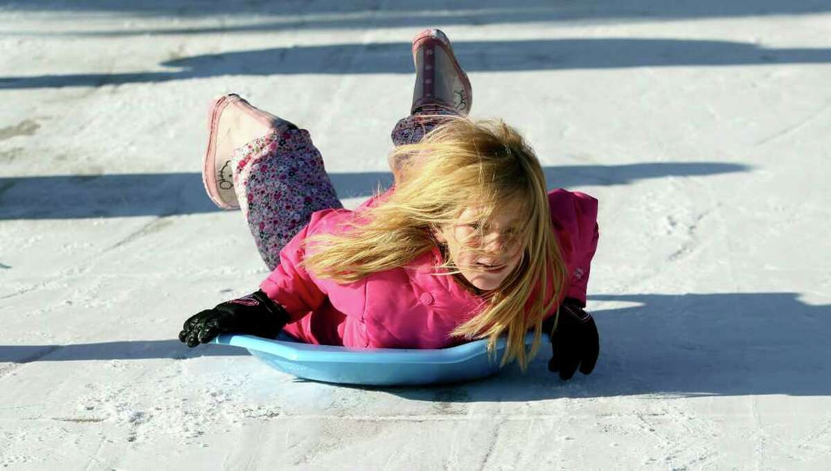 METRO Addicson Holt doesn't mind the cold as she slides down a driveway in the Gruene Crossing subdivison as snow accumulation shows in the New Braunfels area on February 4, 2011. Tom Reel/Staff