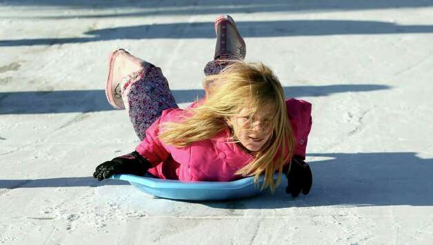 METRO   Addicson Holt doesn't mind the cold as she slides down a driveway in the Gruene Crossing subdivison as snow accumulation shows in the New Braunfels area on February 4, 2011. Tom Reel/Staff Photo: TOM REEL, SAN ANTONIO EXPRESS-NEWS / © 2010 San Antonio Express-News