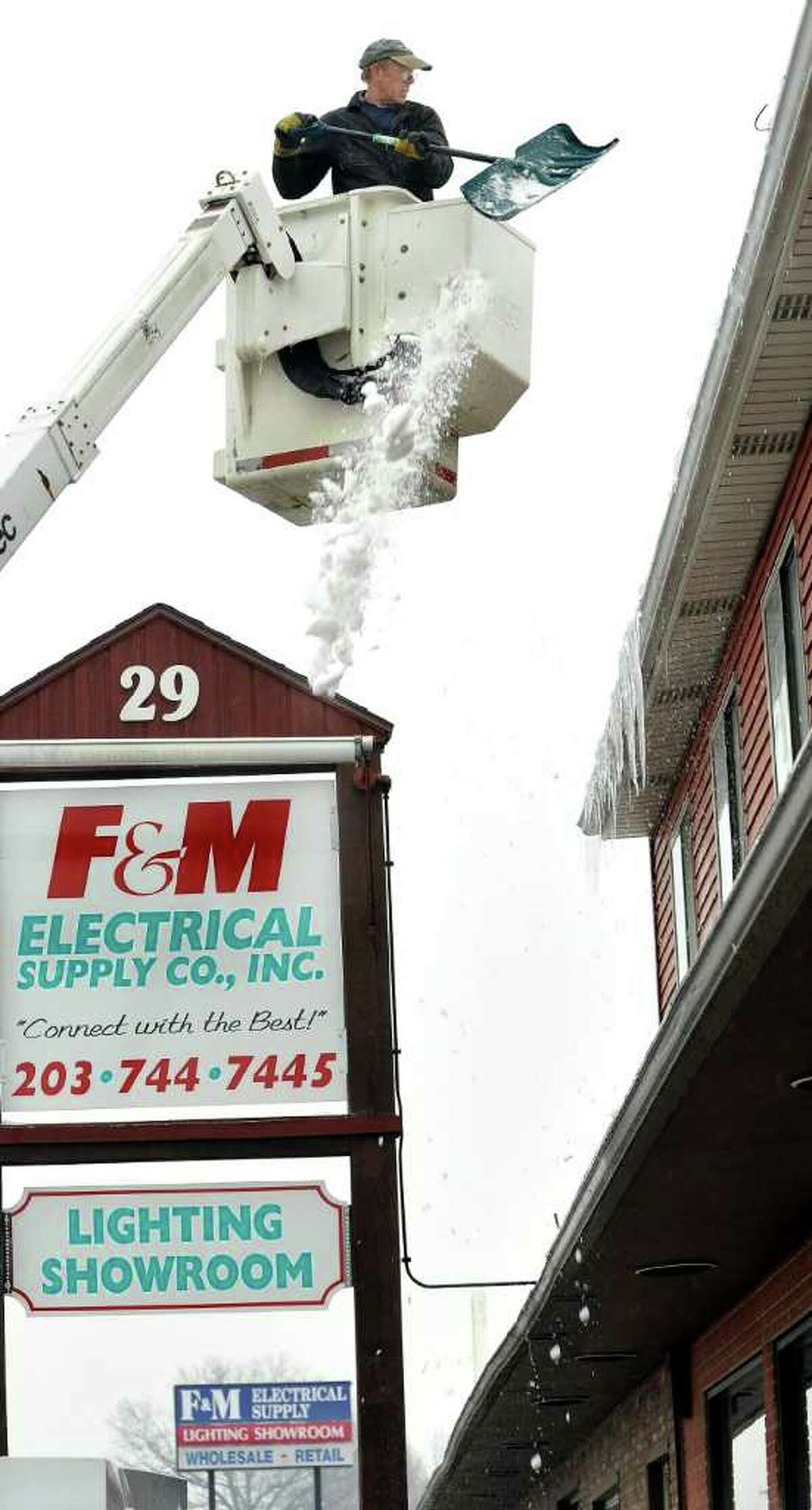 Larry Giddings, of JAR Associates in Danbury, clears snow from the roof of a local business, Saturday, Feb. 5, 2010.