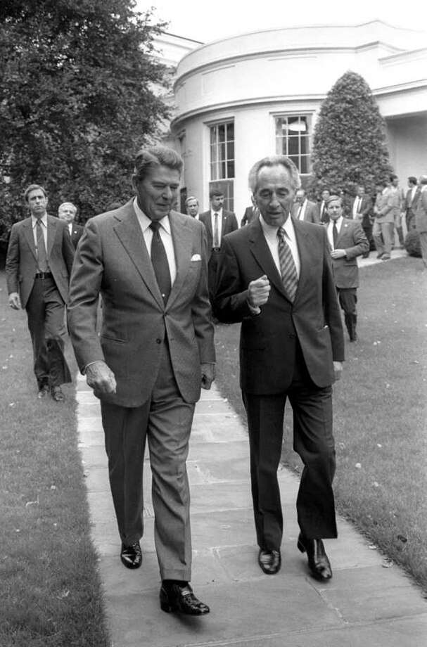 WASHINGTON, D.C: (FILE PHOTO) US President Ronald Reagan (L) accompanies Israeli Prime Minister Shimon Peres to his car after their meeting in the White House October 9, 1984 in Washington, DC. Reagan, the nation's longest living president, battled Alzheimer's disease for the past decade and passed away age 93, June 5, 2004 at his home in Bel Air, California. (Photo by Herman Chanania/GPO via Getty Images) Photo: Getty Images / Getty Images