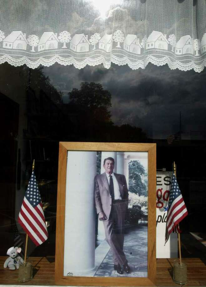 "TAMPICO, IL - JUNE 6:  A picture of former U.S. President Ronald ""Dutch"" Reagan sits in the window of a storefront next door to his birthplace June 6, 2004 in Tampico, Illinois. Reagan died June 5 at his home in California of old age after a long battle with Alzheimer's disease at the age of 93.  (Photo by Scott Olson/Getty Images) Photo: Scott Olson, Getty Images / Getty Images"