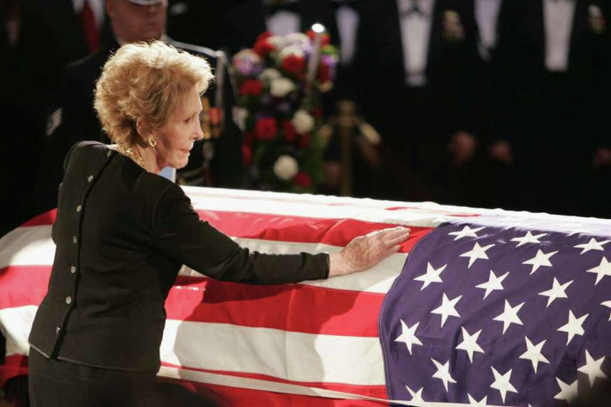 WASHINGTON - JUNE 9: Former first lady Nancy Reagan touches the casket of her husband, former U.S. President Ronald Reagan, during his state funeral on Capitol Hill June 9, 2004 in Washington, DC. Reagan's body will lie in state throughout the night until June 10. (Photo by Peter Jones-Pool/Getty Images)
