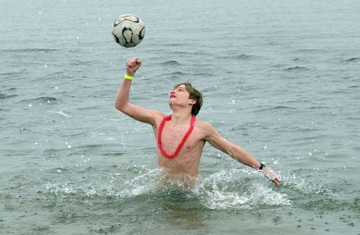 Thirteen-year-old Will Steinharter, of Weston, bounces around a soccer ball while taking a dip in the Long Island Sound during the Burroughs Community Center's fourth annual Freezin' for a Reason plunge Saturday, Feb. 5, 2011 at Jennings Beach in Fairfield.