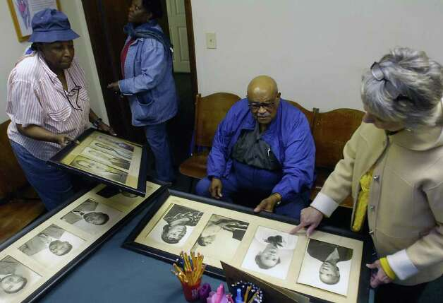 Church members Eddie Ruth Hanks, left, and Margie Mays, bring in more church portraits, taken by Alonzo Jordan, that were stored in a closet, for Reverend John D. Hardin, middle, and Nina Messersmith, right, to see. The portraits will be hung in the room of the church as soon as possible.   Dave Ryan/The Enterprise Photo: Dave Ryan / Beaumont