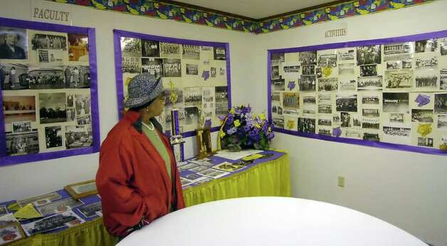 In a room at the Lonestar Youth Council Community Center, dedicated to the memories of the J. H. Rowe High School Tigers, Willie Fay McFarland looks at the collection of photographs, many taken by  community photographer Alonzo Jordan, that graduates had put together as keepsakes.  Dave Ryan/The Enterprise / Beaumont