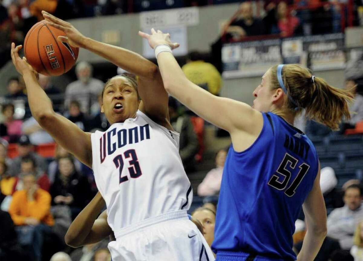 Connecticut's Maya Moore, left, is fouled by DePaul's Katherine Harry during the first half of an NCAA college basketball game, in Storrs, Conn., Saturday, Feb. 5, 2011. (AP Photo/Jessica Hill)