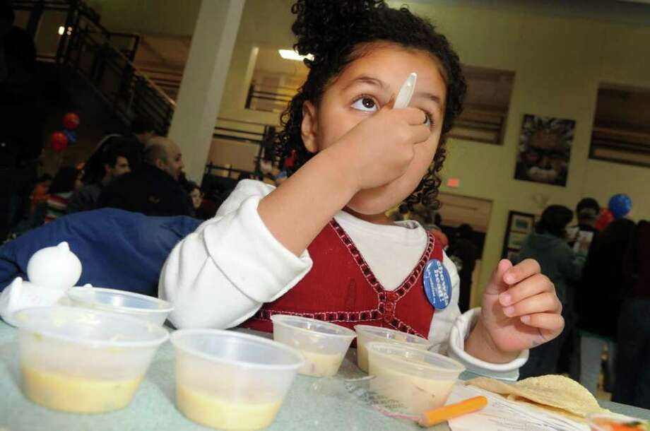 "Four-year-old Gracie Shaw-Rothberg, of Brooklyn, NY, samples a variety of chowders Saturday, Feb. 5, 2011 during the annual ""Chowdafest"" competition at Bedford Middle School in Westport, to benefit the Connecticut Food Bank. Photo: Autumn Driscoll"